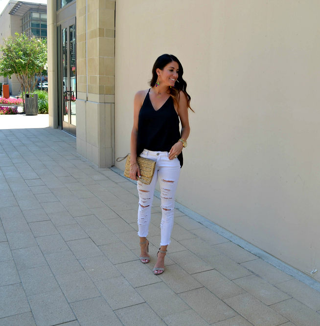 white jeans, black top, gold clutch